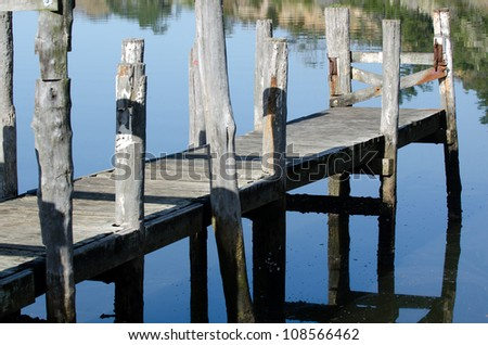 An empty wharf pier on a calm river in New Zealand . - stock photo