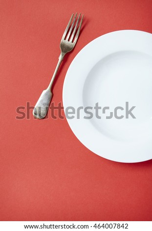 An empty white dinner dish and fork on a red background