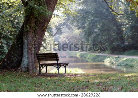 An empty wooden bench over looks a river on a sunny summer day. - stock photo