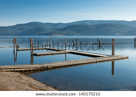 An empty wooden boat dock in late summer with haze around the mountains across the calm lake. - stock photo