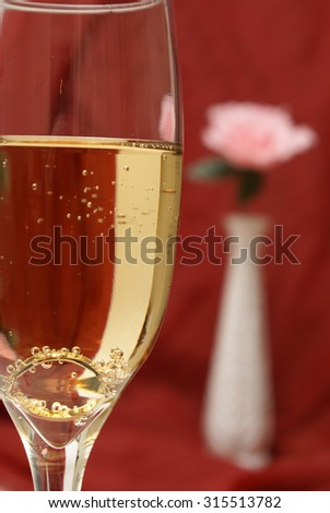 An engagement ring is set inside a glass of champagne to ask the big question. - stock photo