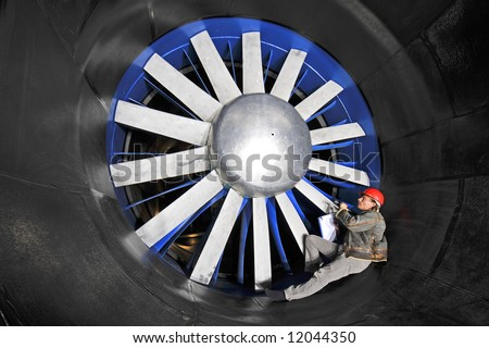An engineer, checking up on the mechanical structure inside a wind tunnel - stock photo