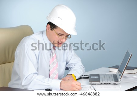 An engineer with white helmet at work  on gray background - stock photo