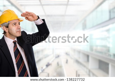 An engineer with yellow hardhat at the office - stock photo