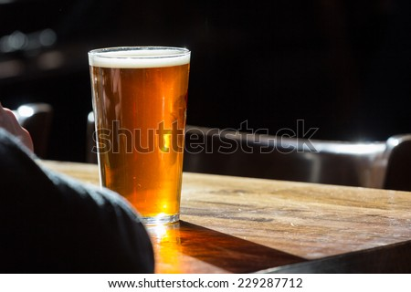 An english ale in front of an individual on a wooden table in a pub in London, UK - stock photo