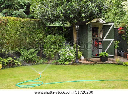 An English back garden being watered with a hosepipe and spray - stock photo
