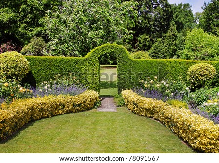 An English Landscape Garden in early Summer with flowerbeds and an Arch through a Hedgerow - stock photo