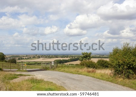 an english landscape with a country road and a cattle grid under a blue cloudy summer sky