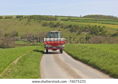 an english landscape with a tractor with fertilizer spreader attached traveling along a quiet country road in the yorkshire wolds - stock photo