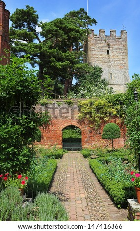 An English walled garden against a blue summer sky with Church steeple - stock photo