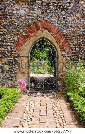 An English Walled garden with arched entrance through the Wall - stock photo