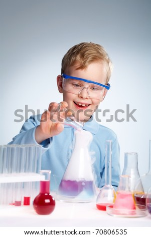 An enthusiastic boy looking at the results of his experiment - stock photo