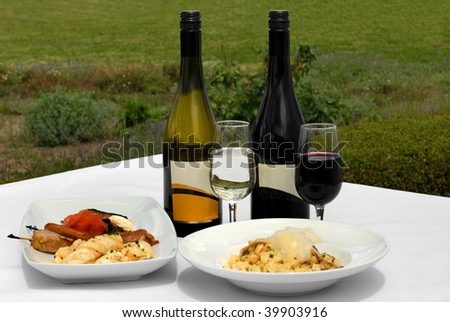 An Entree tasting plate, and a bowl of Mushroom Risotto, accompanied by a glass of Chardonnay