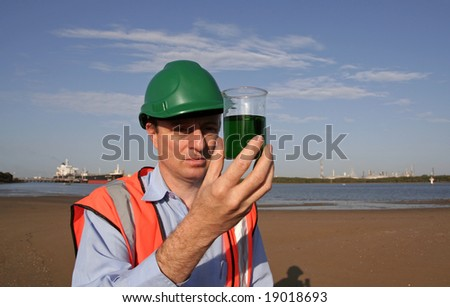 An environmental engineer on the mudflats examining a sample of oil from the ship docked behind him, showing the estuary and beautiful blue sky, wearing orange reflective vest and green safety helmet - stock photo