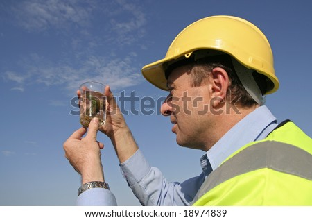 An environmental engineer, wearing protective clothing, and a yellow hard hard examining a sample into a specimen jar, with a beautiful blue sky behind him - stock photo