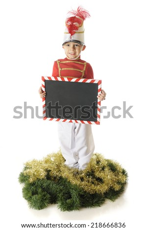 An erect preschool Christmas soldier holding a candy cane striped chalkboard (left blank for your text).  On a white background. - stock photo