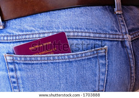 An EU/UK passport pokes out of the rear pocket of someone's jeans. A temptation for a pickpocket. - stock photo
