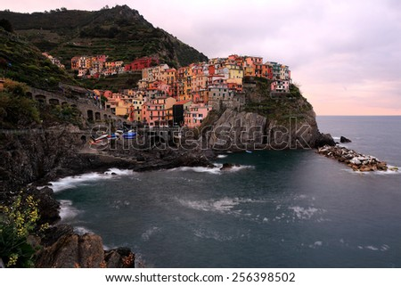 An evening view of Manarola on vertical cliffs -- an amazing village in Cinque Terre, Italy - stock photo