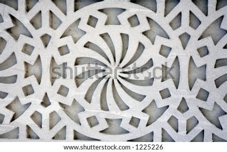 An example of Islamic design cast in concrete on a building in Doha, Qatar, crudely painted white. As Islam bans the depiction of human or animal forms, artists developed their style using shapes. - stock photo