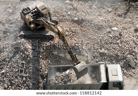 An excavator loading a truck after demolishing houses for reconstruction - stock photo