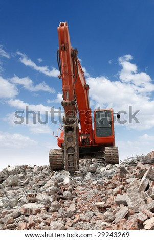 An excavator with a hydraulic hammer attachment in a destruction area. - stock photo