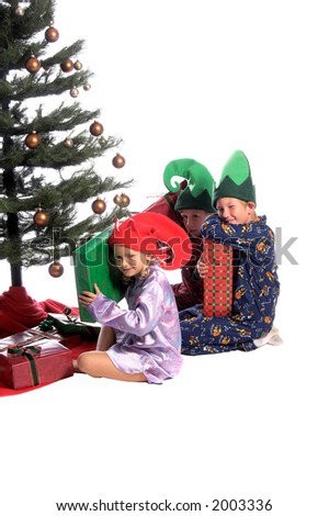 An excited group of children sitting under the Christmas Tree as examining the presents