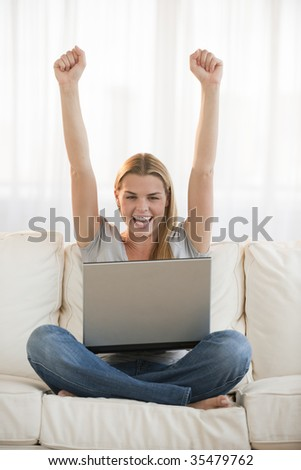 An excited looking young blonde raising her fists in the air and cheering.  She is smiling and has a laptop computer in her lap.  Vertically framed shot.