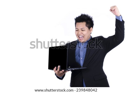 An excited man holding a laptop and raising arm in clenched fist and looking upward celebrates victory, achievement or success. - stock photo