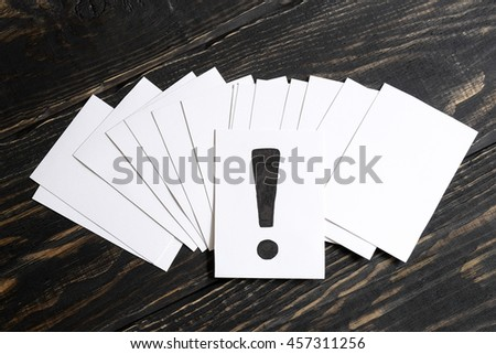 An exclamation mark on table concept for confusion, question or solution on wooden background in the middle - stock photo