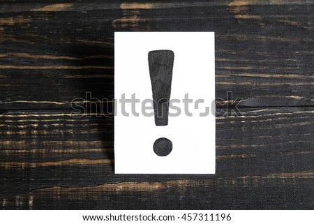 An exclamation mark on the paper on a wooden table in the middle - stock photo