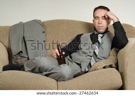 An exhausted businessman is sitting on his sofa at home and having a beer