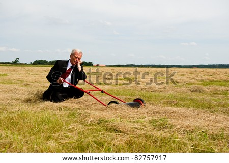 An exhausted businessman rest on his knees with his lawnmower in a field of harvested grain as he prepares to reap the rewards of all his hard labour and perseverance, conceptual image - stock photo