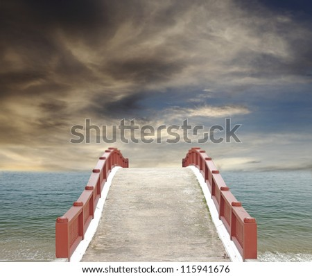 An exotic masonry bridge leading into the horizon of a turquoise sea against a surreal dramatic sunset. - stock photo