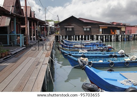 An exotic timber jetty with wooden sampan boat anchored to the pier in the Chew Jetty, which is a UNESCO heritage site, in Penang, Malaysia. - stock photo