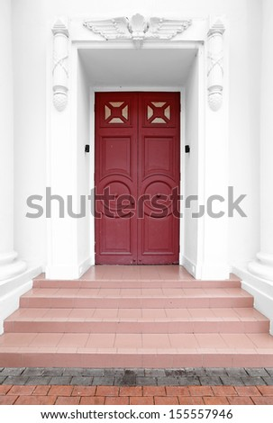 An exotic vintage timber panel door in a ornate frame doorway.  - stock photo
