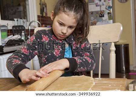 An Experienced Roller. A young girl shows her skill and experience in using a rolling pin. She evenly distributes her weight along the pin to properly roll the gingerbread dough flat. - stock photo
