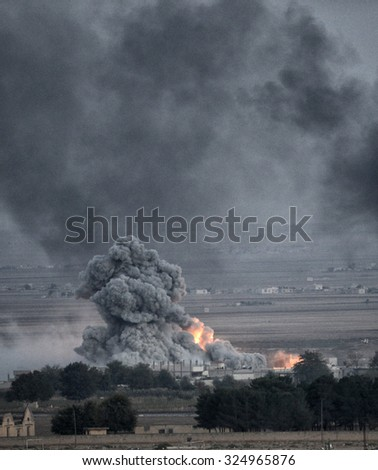 An explosion after an apparent US-led coalition airstrike on Kobane, Syria, as seen from the Turkish side of the border, near Suruc district, 24 October 2014, Sanliurfa, Turkey  - stock photo