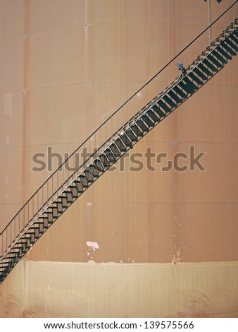 An external staircase curves to the top of an industrial fuel tank. - stock photo