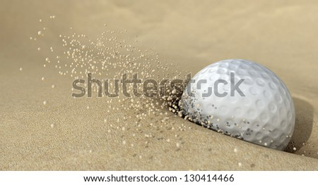 An extreme close up of a golf ball hitting the sand in a bunker and emitting grains of sand forwards - stock photo