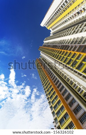 An extreme low angle shot of a new colorful high rise apartment against the sky. - stock photo