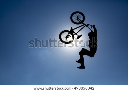 An extreme rider is making a free style jump from a ramp. The young boy with his bicycle is seen as a silhouette in front of the sun.