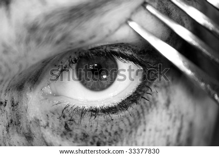 an eye threatened with a knife