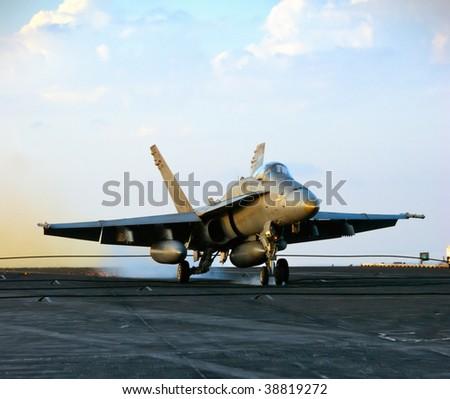 An F-18 Hornet lands aboard an aircraft carrier - stock photo