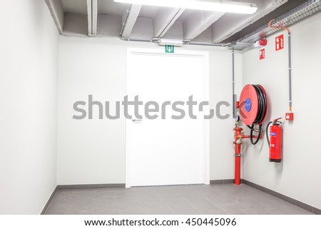 an fire hose hanging on the wall and powder extinguisher - stock photo