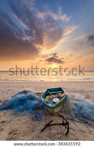 An fishing boat with its fishing net and cloudy sky with colorful sunset on Karon beack in Phuket Thailand - stock photo