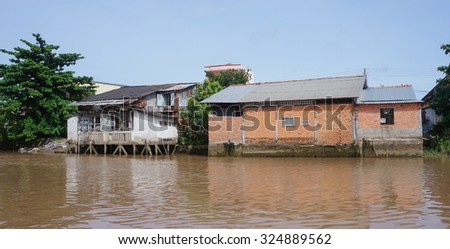 An Giang, Vietnam - Nov 30, 2014. Houses of local people staying along river in Mekong delta, southern Vietnam.  - stock photo