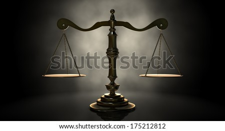 An gold justice scale backlit on an eerie dark background - stock photo