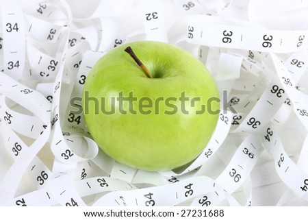 an green apple and a measure tape; isolated on white - stock photo