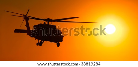 An H-60 seahawk (or blackhawk) helicopter flies low against a setting sun in the middle east