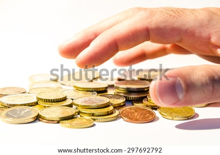 an hand is grabbing a group of different coins, (euro and cents), europe currency, over white - stock photo